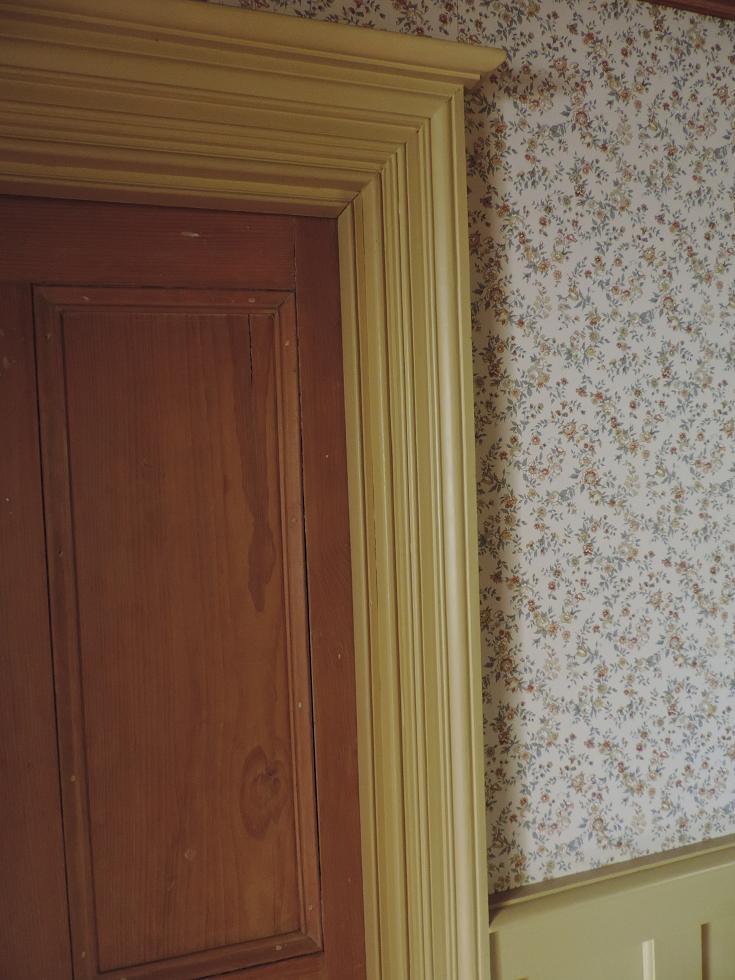 Un chambranle et sa corniche entourant une porte intérieure.