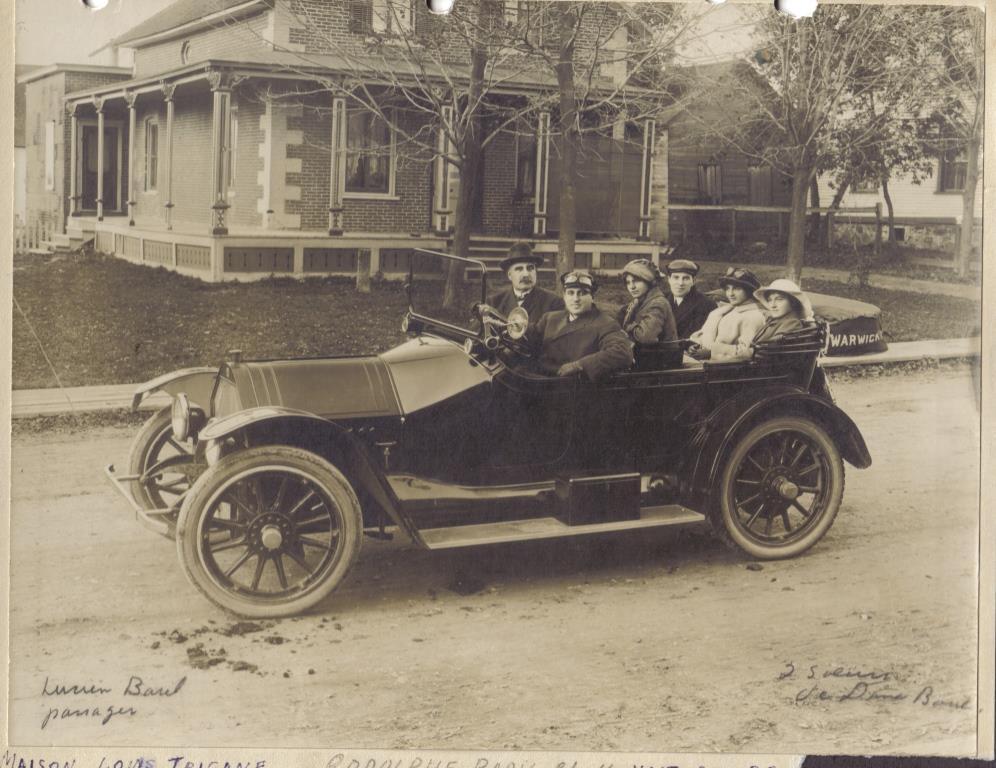 Rodolphe Baril conduisant une auto Mitchell (vers 1915 ?). Son beau-père, monsieur Médard Luneau est assis à sa droite. Au centre, madame Augustine Luneau, son épouse et à l'arrière à droite, son frère Lucien avec deux sœurs de madame Luneau.