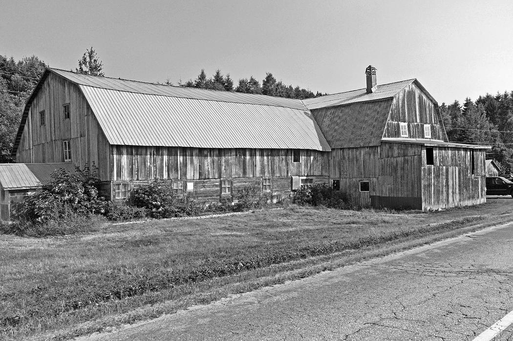 Grange de style à comble brisé de Charlevoix, regroupement dans un seul édifice des bâtiments-blocs (milieu du 20e).