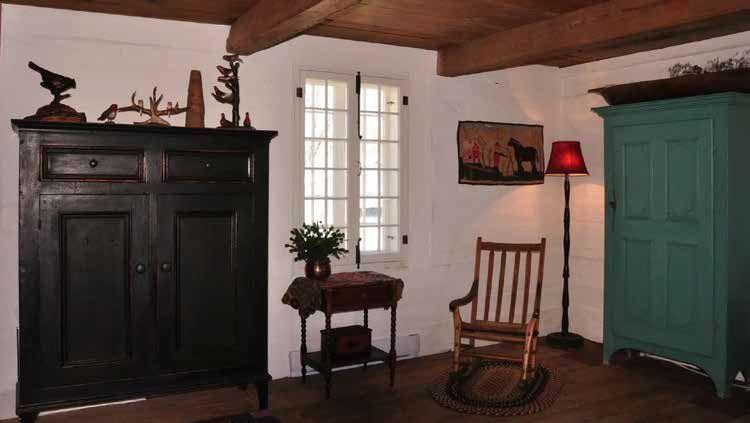 Les murs de pièces chaulés à l'ancienne éclairent la pièce et mettent en évidence les meubles anciens. Photo : Marjolaine Mailhot.
