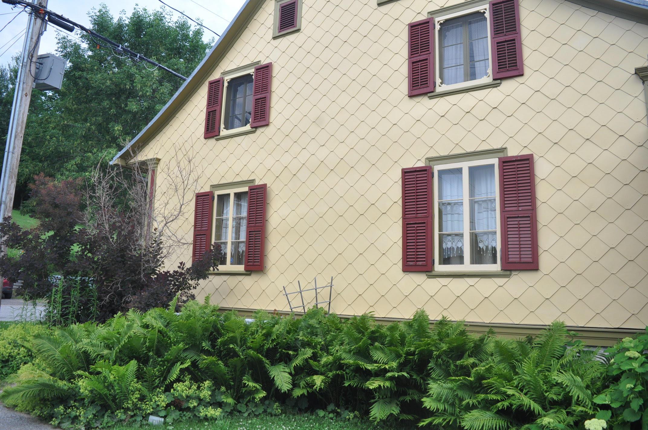 Maison du 19è siècle située à Grondines, couverte de panneaux d'amiante-ciment en forme de losanges. Les fenêtres d'origine sont munies de jalousies © Clément Locat